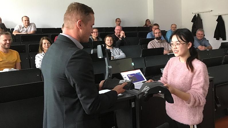 Vor Publikum wird der Studentin ein Geschenk übbereicht.